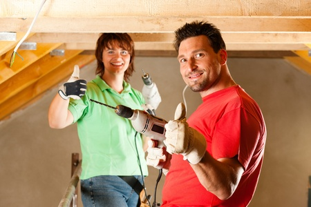 home renovation: DIY couple in home improvement with hand drill standing on a scaffold