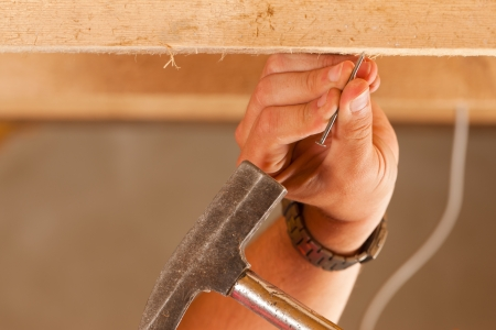 Construction worker - only hand to be seen - with hammer and nail    Stock Photo - 10330251