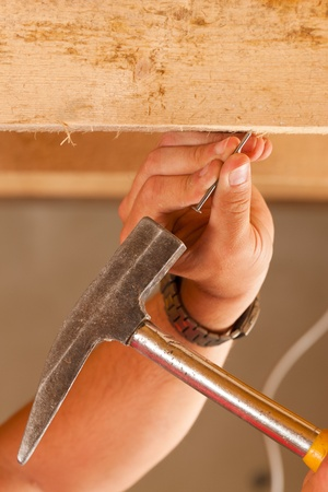 banging: Construction worker - only hand to be seen - with hammer and nail