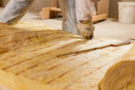 Man - seule main pour être vu - la coupe de la laine de verre comme matériau pour l'isolation thermique d'un nouveau bâtiment Banque d'images