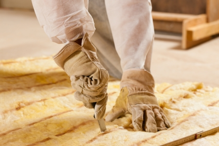 thermal insulation: Man - only hand to be seen - cutting some glass wool as material for thermal insulation of a new building