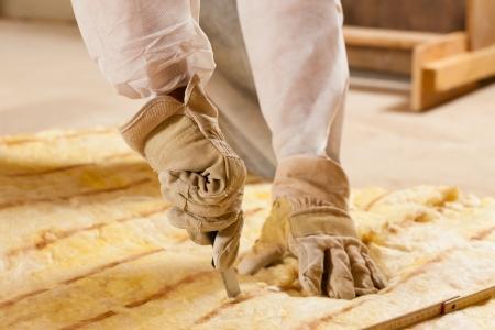 Man - tylko ręka być postrzegane - cięcie trochę wełny szklanej jako materiału do izolacji cieplnej w nowym budynku
