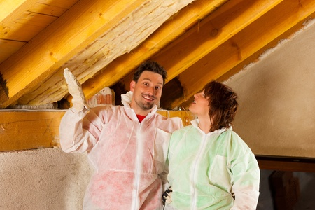 Couple installing thermal insulation thru glass wool on their roof, they are looking pretty proud