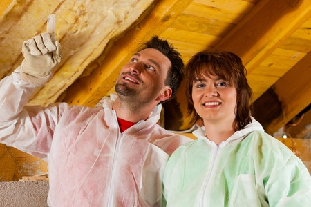 attic: Couple installing thermal insulation thru glass wool on their roof, they are looking pretty proud