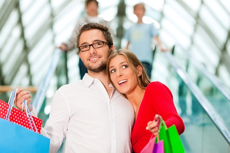 shopping man: Couple - man and woman - in a shopping mall with colorful bags on an escalator Stock Photo