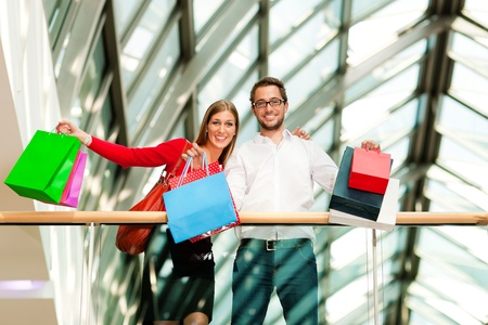 Couple - man and woman - in a shopping mall with colorful bags looking at their bought stuff photo