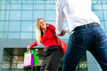 dragging: Woman wants to shop into mall, dragging her man or boyfriend to join   Stock Photo