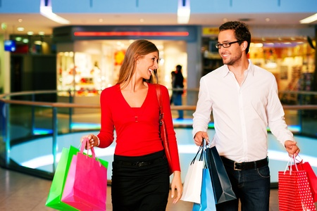 consume: Couple - man and woman - in a shopping mall with colorful bags simply having fun