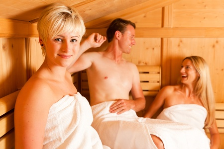 Three people (one male, two female) enjoying a hot sauna, having a casual chat Stock Photo - 10428251