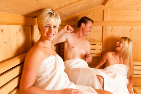 Three people (one male, two female) enjoying a hot sauna, having a casual chat   photo