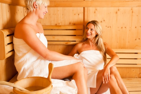 Two women enjoying a hot sauna, having a casual chat Stock Photo - 10428252