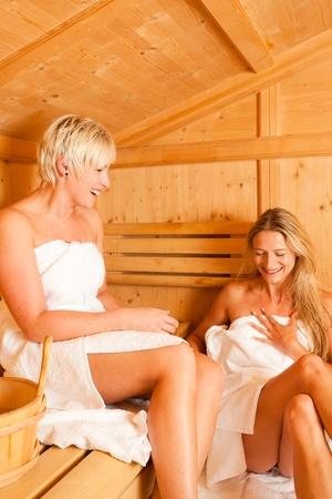 Two women enjoying a hot sauna, having a casual chat Stock Photo - 10428311