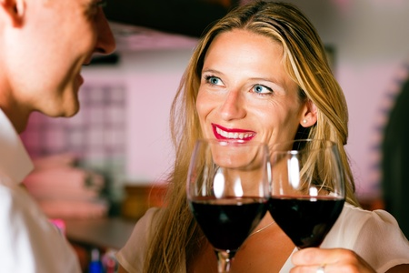 Man and woman in a hotel bar in the evening having glasses of red wine and a little flirt Stock Photo - 10428309