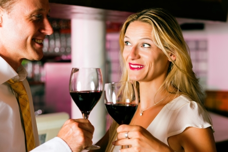 Man and woman in a hotel bar in the evening having glasses of red wine and a little flirt Stock Photo - 10428259