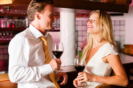 Man and woman in a hotel bar in the evening having glasses of red wine and a little flirt Stock Photo - 10428248