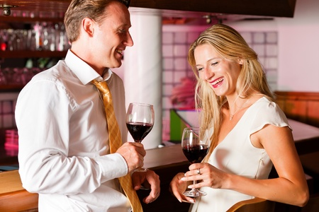 Man and woman in a hotel bar in the evening having glasses of red wine and a little flirt Stock Photo - 10428262