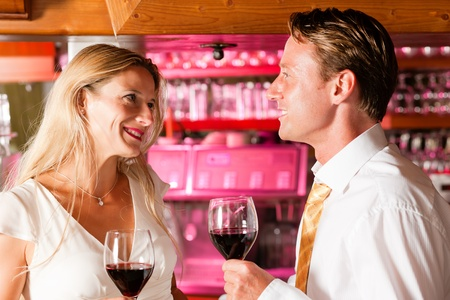 Man and woman in a hotel bar in the evening having glasses of red wine and a little flirt Stock Photo - 10428249
