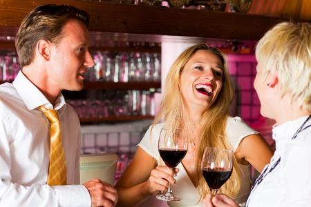 bebiendo vino: Hombre y dos mujeres en un hotel de bar en la noche con vasos de vino tinto y probablemente un poco coquetear