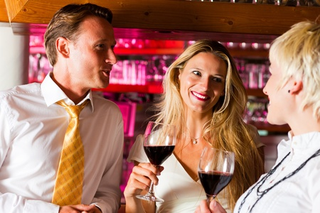 Man and two women in a hotel bar in the evening having glasses of red wine and probably a little flirt Stock Photo - 10428315