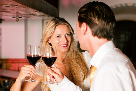 Man and woman in a hotel bar in the evening having glasses of red wine and a little flirt Stock Photo - 10428256