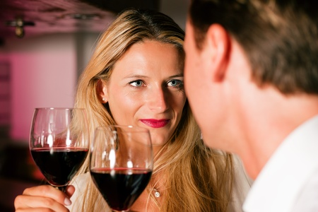 Man and woman in a hotel bar in the evening having glasses of red wine and a little flirt Stock Photo - 10428253