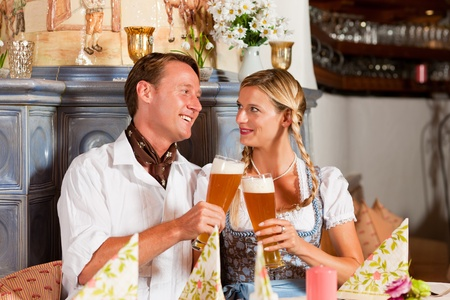 tracht: Couple in Bavarian Tracht drinking wheat beer in a typical pub, clinking glasses