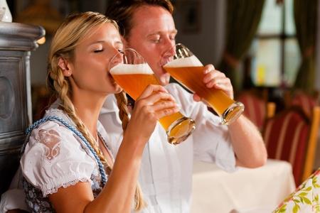 hombre tomando cerveza: Pareja en Tracht bávaro bebiendo cerveza de trigo en una taberna típica Foto de archivo
