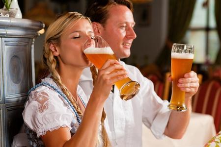 hombre tomando cerveza: Pareja en Tracht bávaro bebiendo cerveza de trigo en una taberna típica