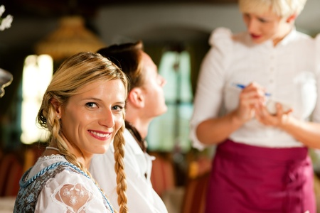 tracht: Couple in Bavarian Restaurant ordering food and drinks from the waitress