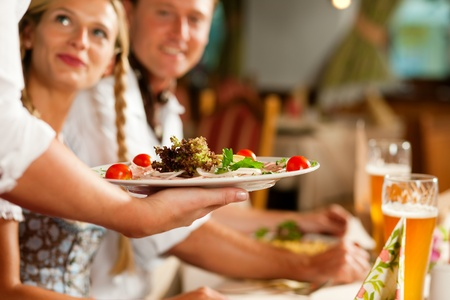 serving: Couple in Bavarian Tracht drinking wheat beer in a typical pub, the waitress is serving the food   Stock Photo