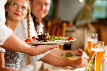 Pareja en Tracht bávaro bebiendo cerveza de trigo en un típico bar, la camarera está sirviendo la comida