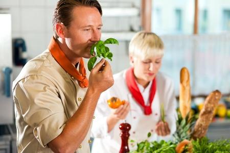 basilic: Deux chefs en �quipe - homme et femme - dans une cuisine de restaurant ou h�tel d�licieux plats de cuisson Banque d'images