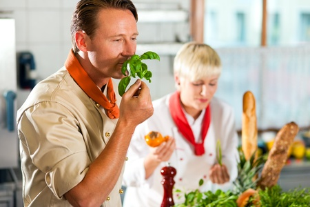 hombre cocinando: Dos cocineros en el trabajo en equipo - hombre y mujer - en un hotel o restaurante cocina cocinar comida deliciosa