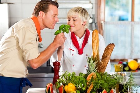 Two chefs in teamwork - man and woman - in a restaurant or hotel kitchen cooking delicious food photo
