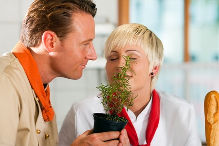 Two chefs in teamwork - man and woman - in a restaurant or hotel kitchen cooking delicious food; they smelling rosemary   Stock Photo - 10428250