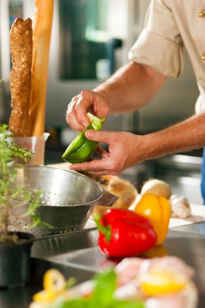 chef cocinando: Cerca de chef en la cocina del restaurante comercial trabajando; él está preparando verduras Foto de archivo