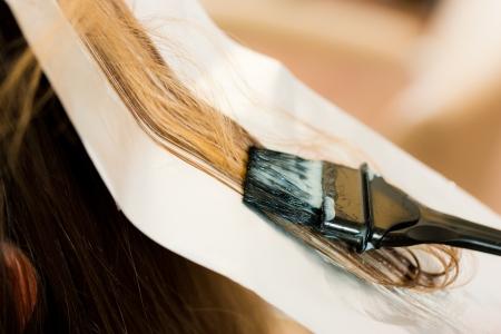 Stylist: A la mujer se pone peluquería nuevo color de pelo, primer plano en la hebra de cabello