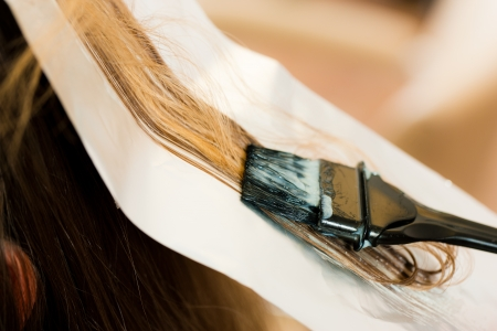 At the hairdresser  woman gets new hair colour, close-up on strand of hair photo