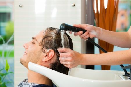coupe de cheveux homme: Homme � la coiffure obtenir ses cheveux lav�s et rinc�s se sentant visiblement bien Banque d'images