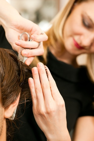 Man at the hairdresser, she is cutting - close-up with selective focus on her hand Stock Photo - 10428060