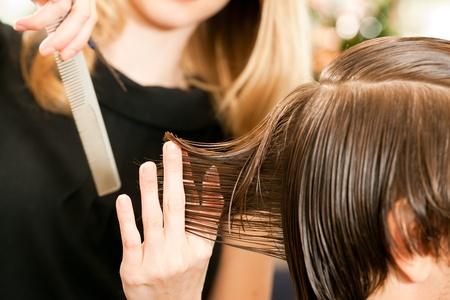 Der Mensch beim Friseur, sie ist Schneiden - close-up mit selektiven Fokus auf die Hand