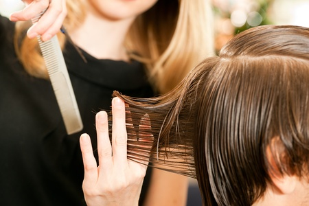 comb hair: Man at the hairdresser, she is cutting - close-up with selective focus on her hand Stock Photo