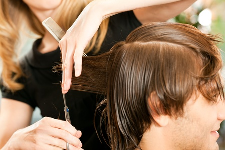 cutting hair: Man at the hairdresser, she is cutting - close-up with selective focus on her hand Stock Photo