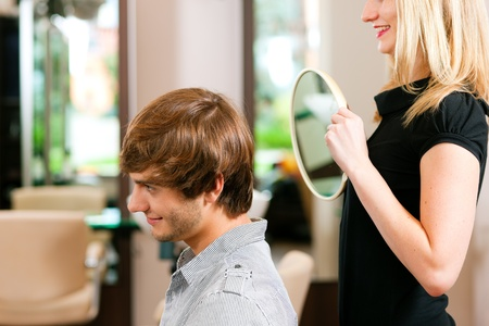 Man at the hairdresser, she has finished the cut and is showing the result in the mirror   Stock Photo - 10428061