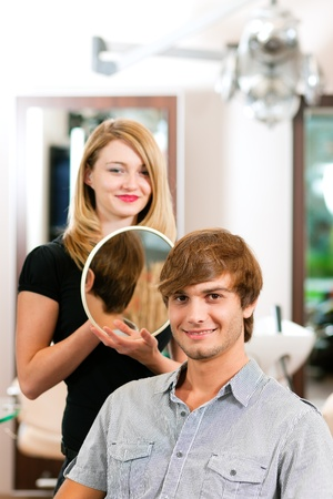 Man at the hairdresser, she has finished the cut and is showing the result in the mirror   photo