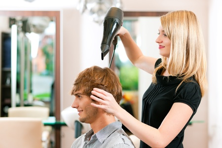 stylist: Man at the hairdresser, she has finished the cut and is drying his hair with a blow dryer Stock Photo