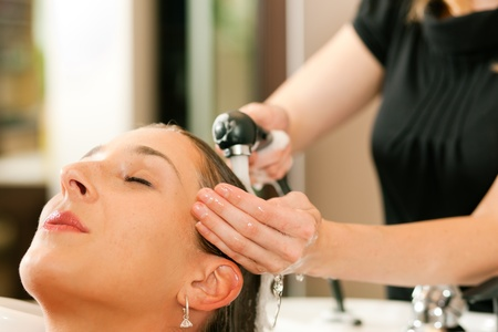 rinsing: Woman at the hairdresser getting her hair washed and rinsed feeling visibly well   Stock Photo