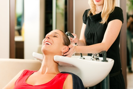 coiffeur: Woman at the hairdresser getting her hair washed and rinsed feeling visibly well   Stock Photo