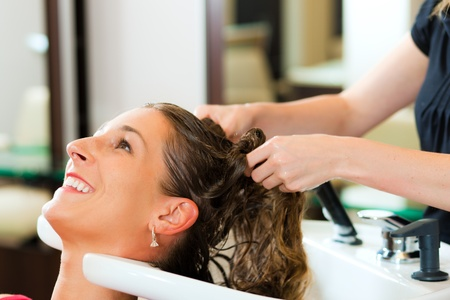 coiffeur: Woman at the hairdresser getting her hair washed and rinsed feeling visibly well