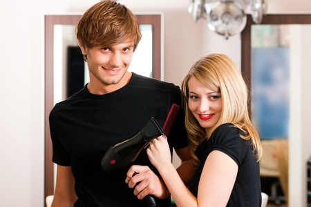 Two hairdresser - man and woman - posing for the camera in the hairdresser Stock Photo - 10428324